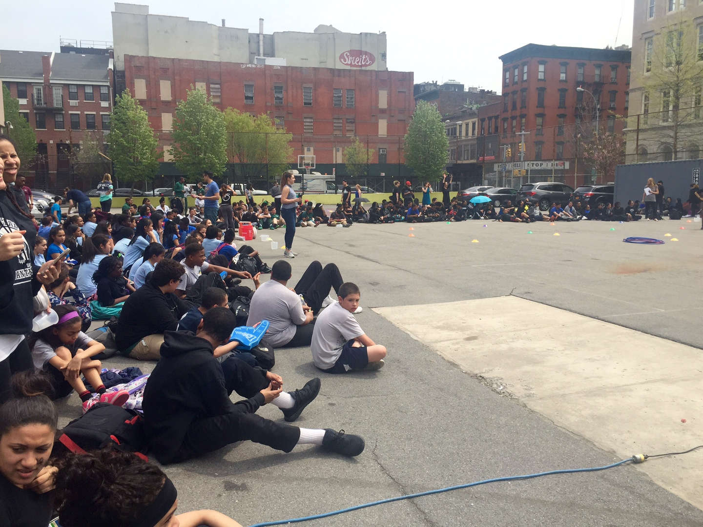 Students sitting down in school yard.