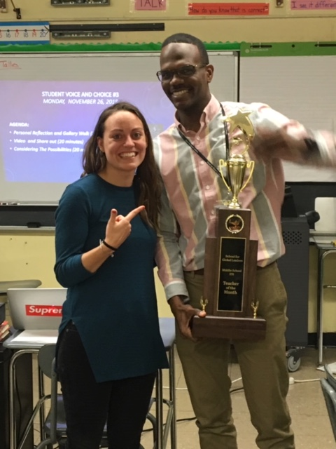 Teacher points to another teaching while handing him a trophy.