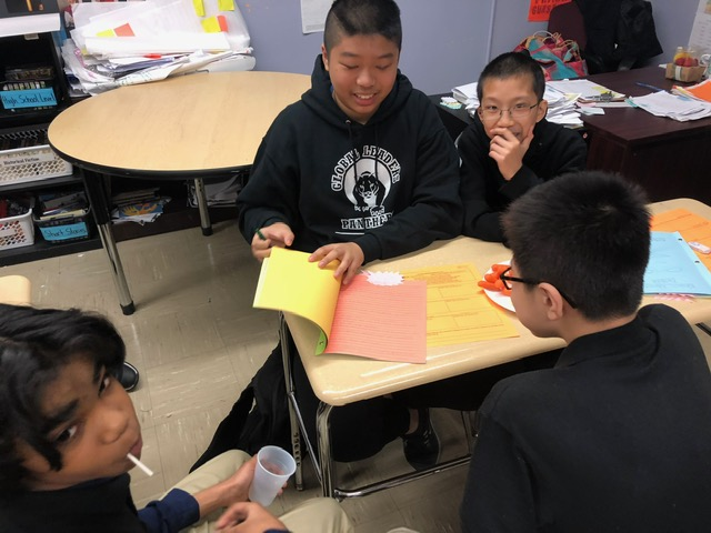 Students at a desk looking at a book.