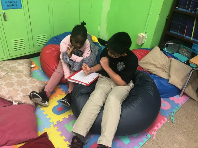 Two students sitting on a bean bag on floor.