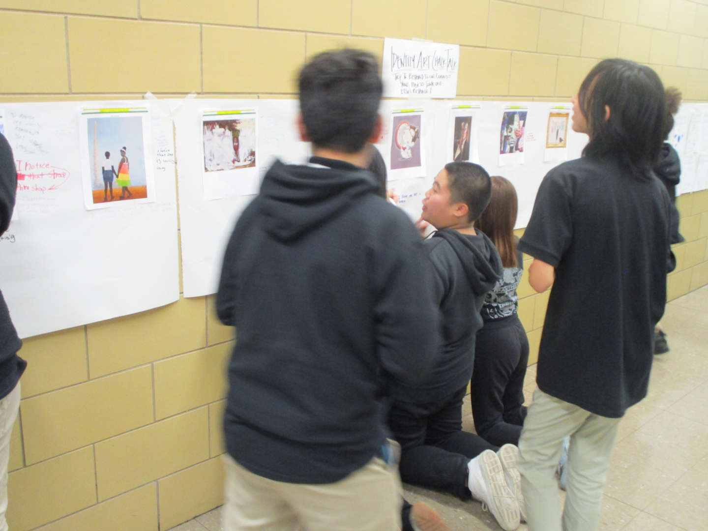 Students looking at artwork in the hallway.