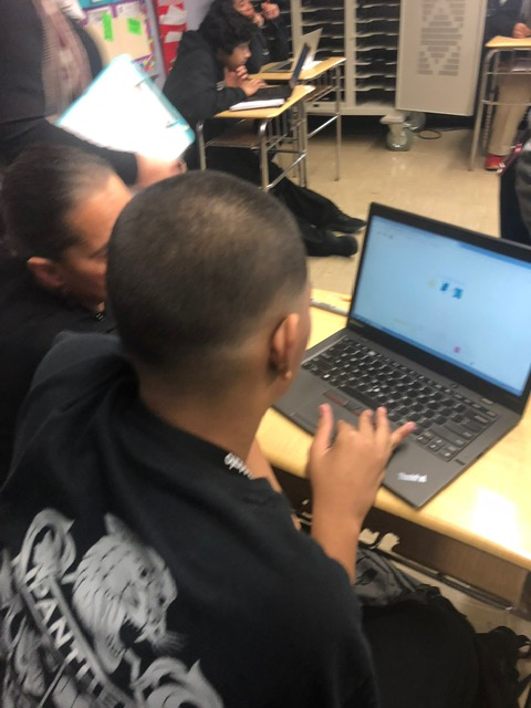 A student is typing on a laptop.