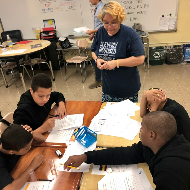 A teacher assists students with work.