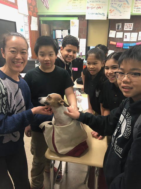 A staff member and students pose with a dog in a bag.