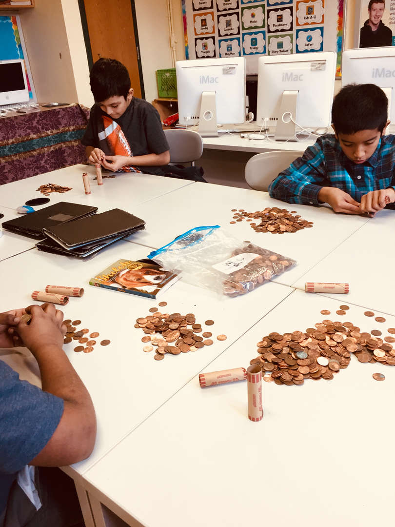 """Student counting Pennies for """"Penny Wars"""" Make a wish foundation."""