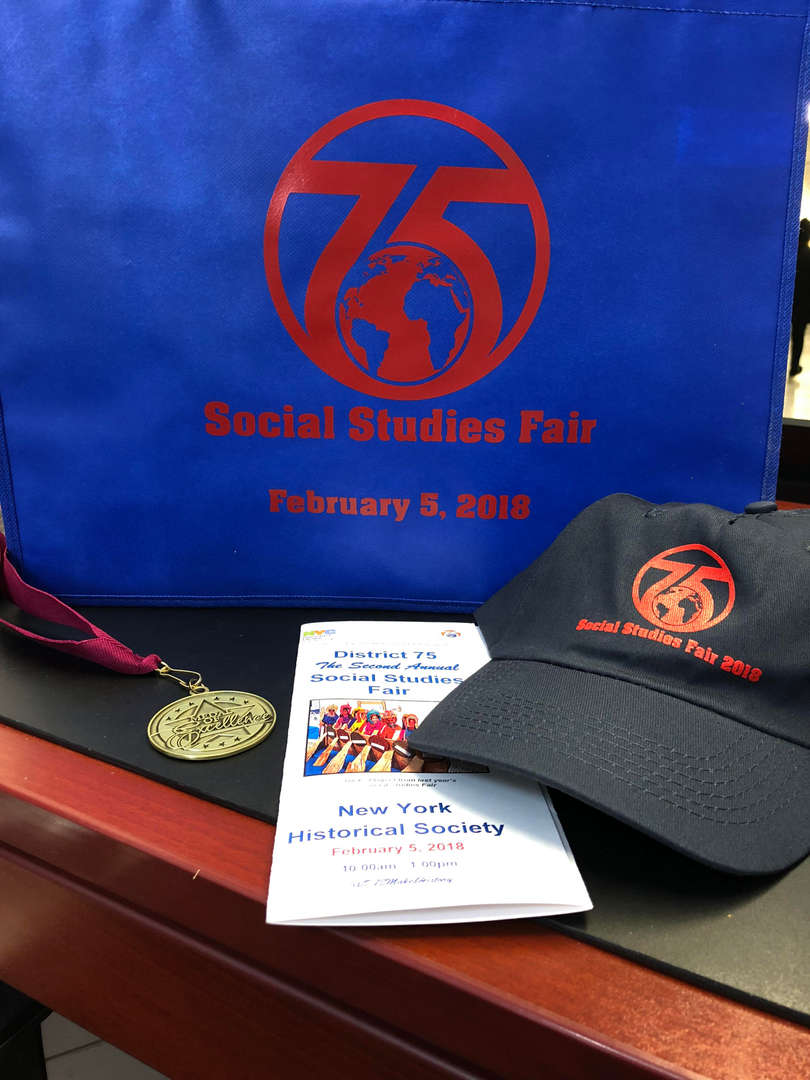 District 75 logo pictured with Social Studies fair awards, a medal, a hat etc.