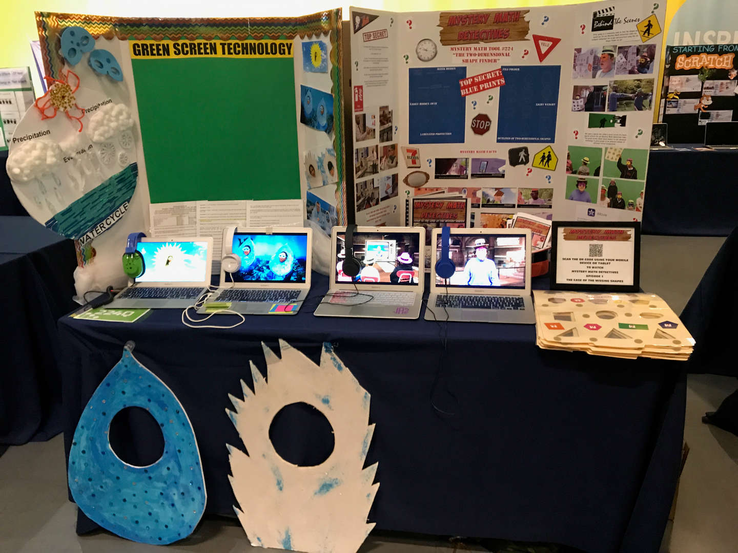 Student projects being displayed on a table.