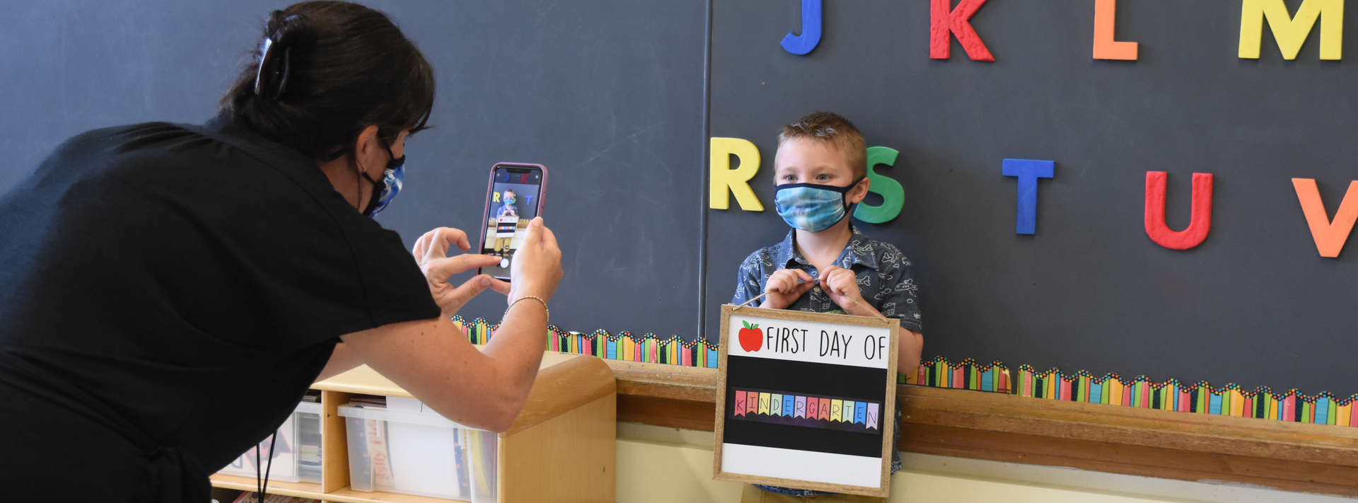 teacher takes a picture of kindergartener