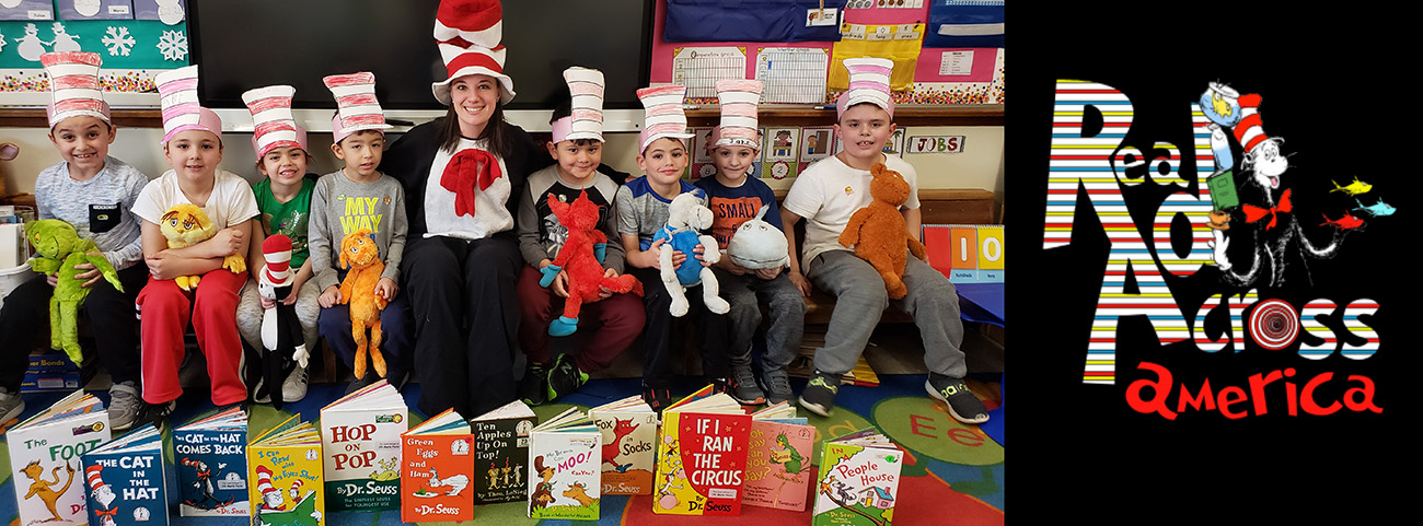 Students and teacher dressed as Dr. Suess characters pose behind books.
