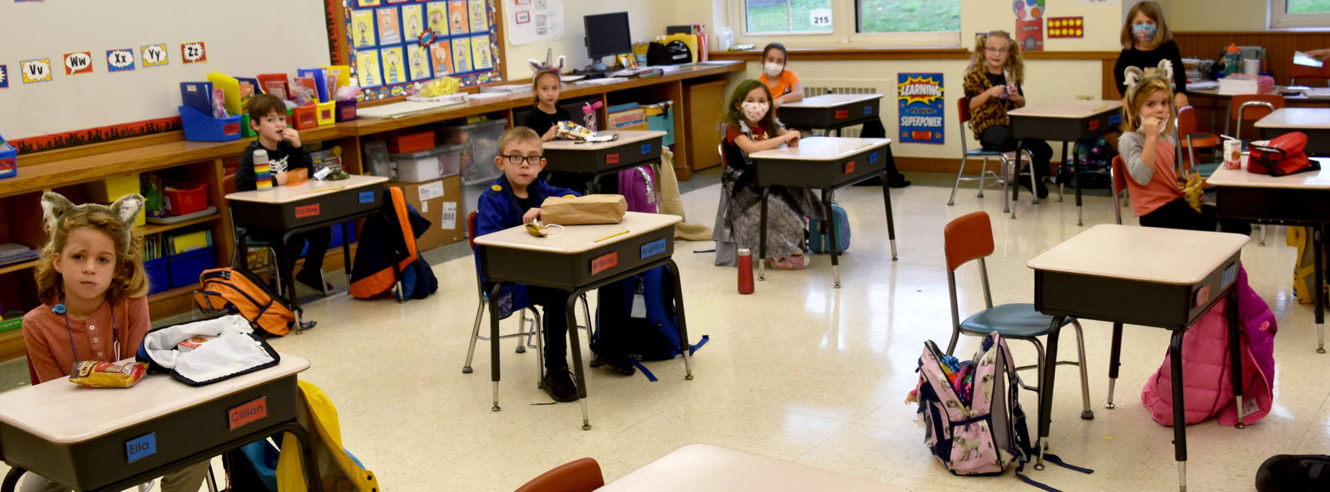 Students sit at their desks eating a snack