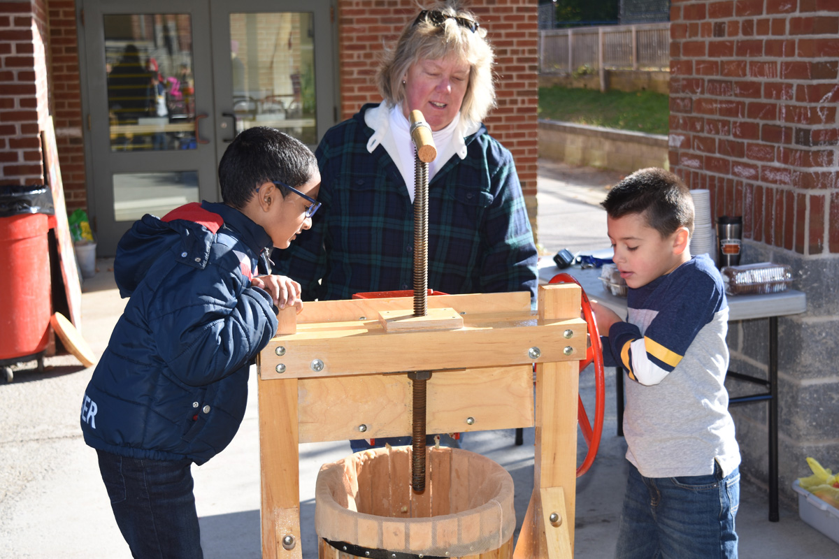 teacher and two boys look into apple press