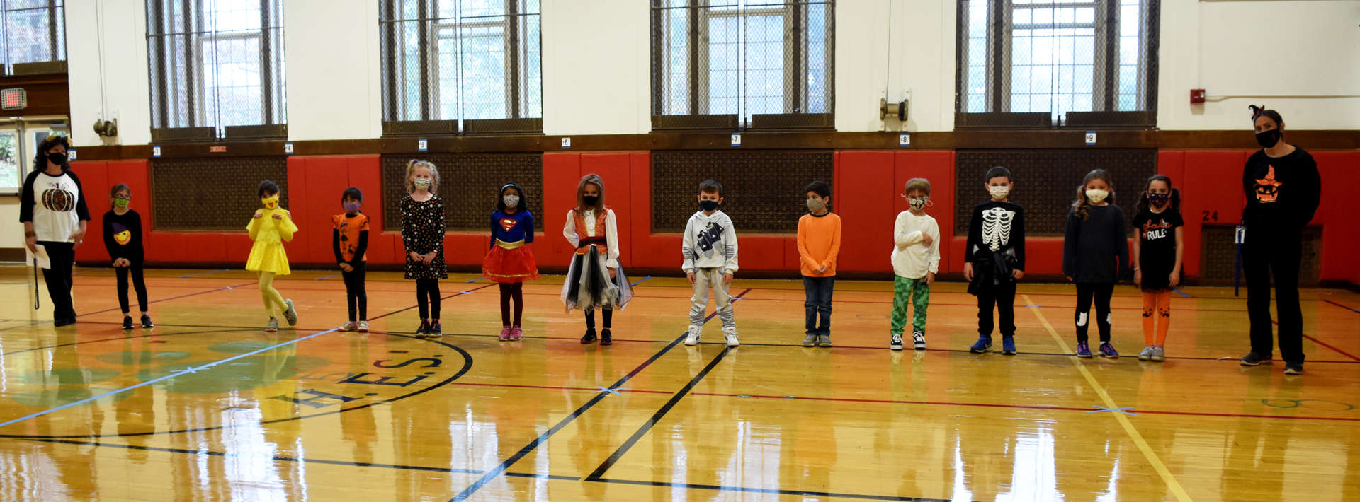 students line up in the gym in their costumes