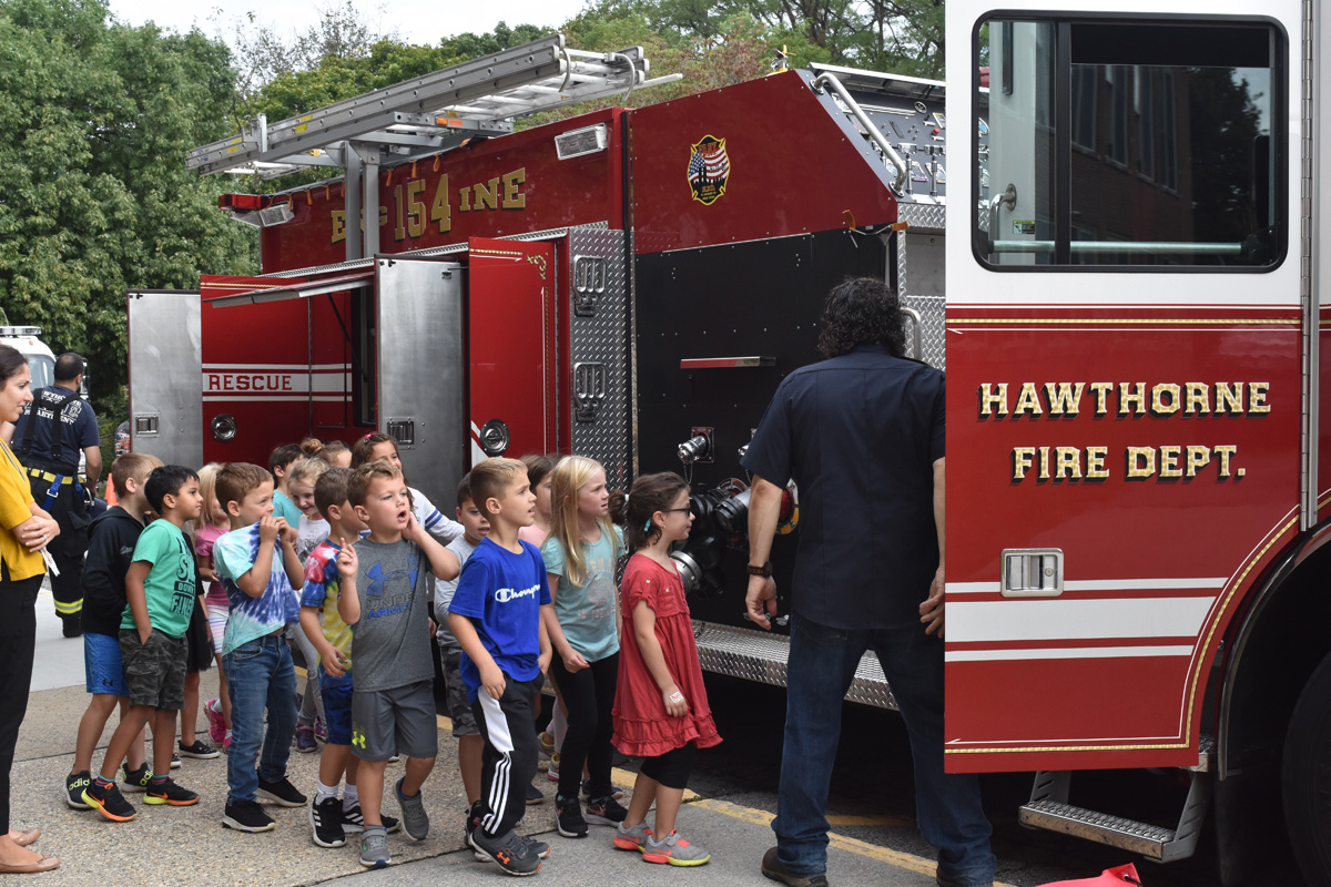 group of students listen to firefighter as he shows them truck