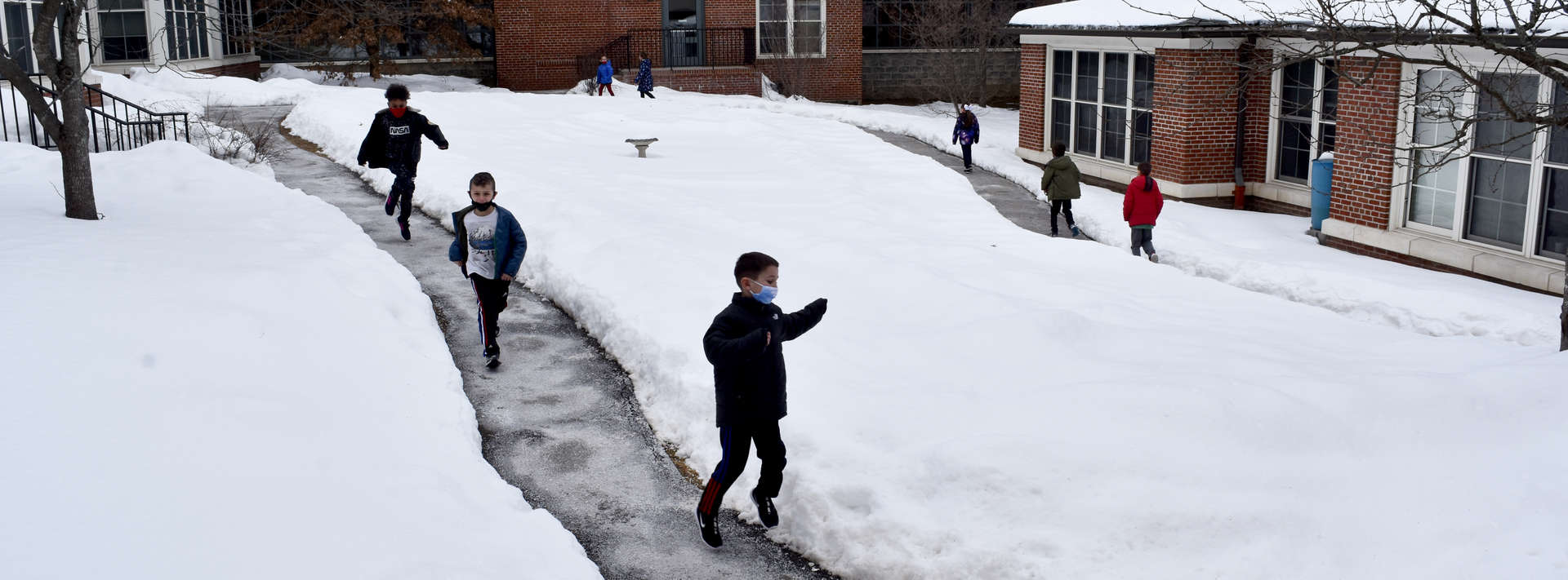 Students running on an outside path around the snow