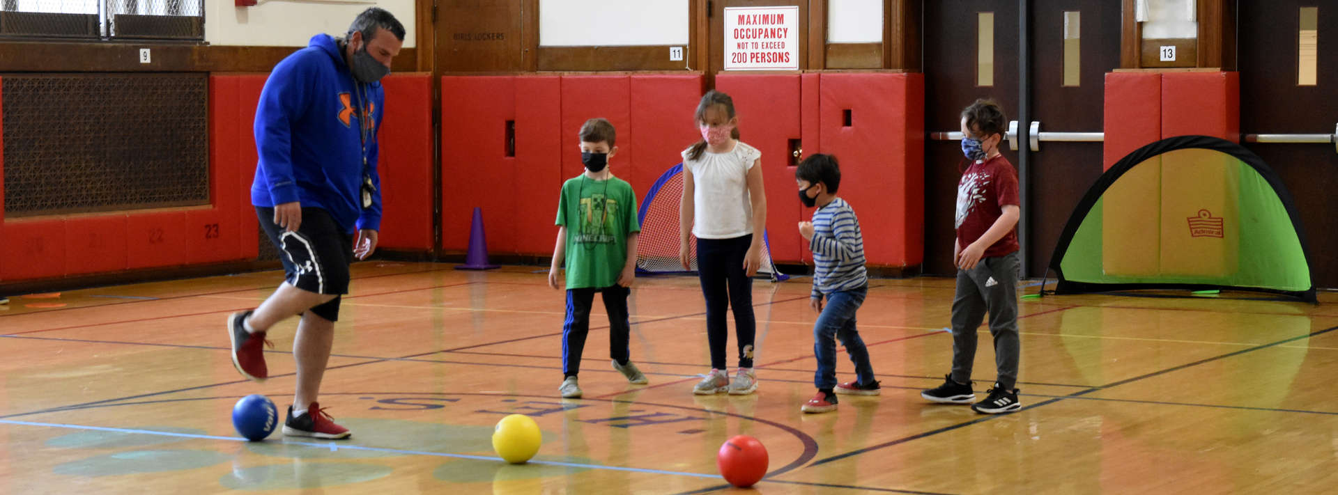 Gym teacher and 4 students playing with colorful balls