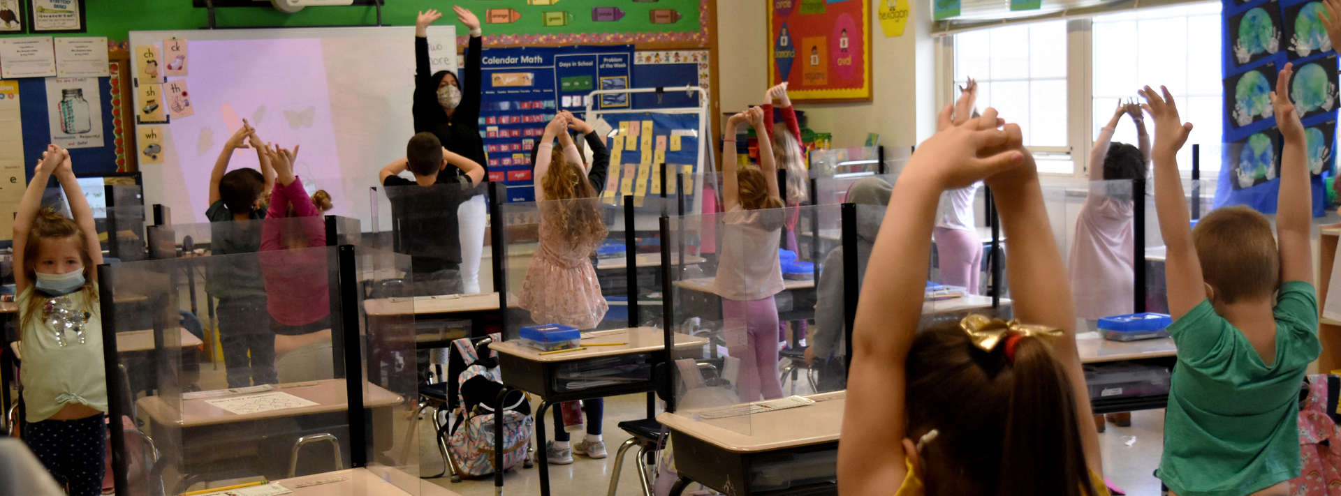 Teacher leading students in class stretching their arms above head