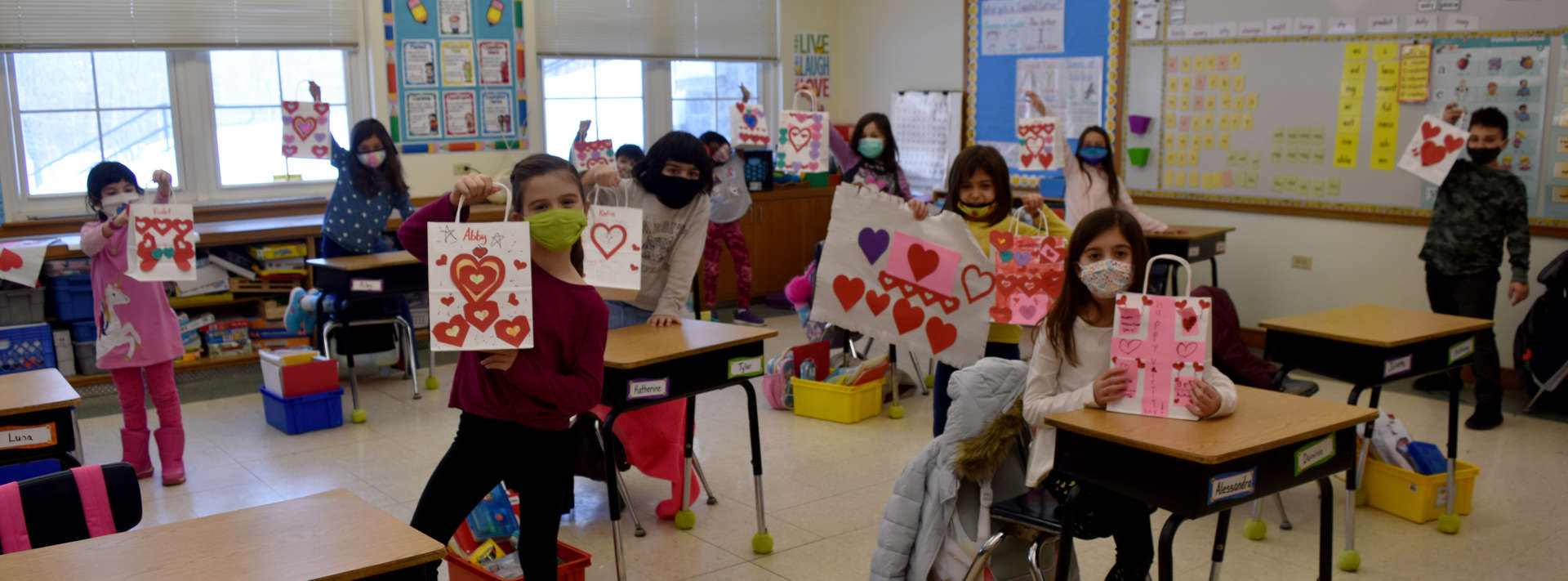 2nd grade students show off their valentine crafts