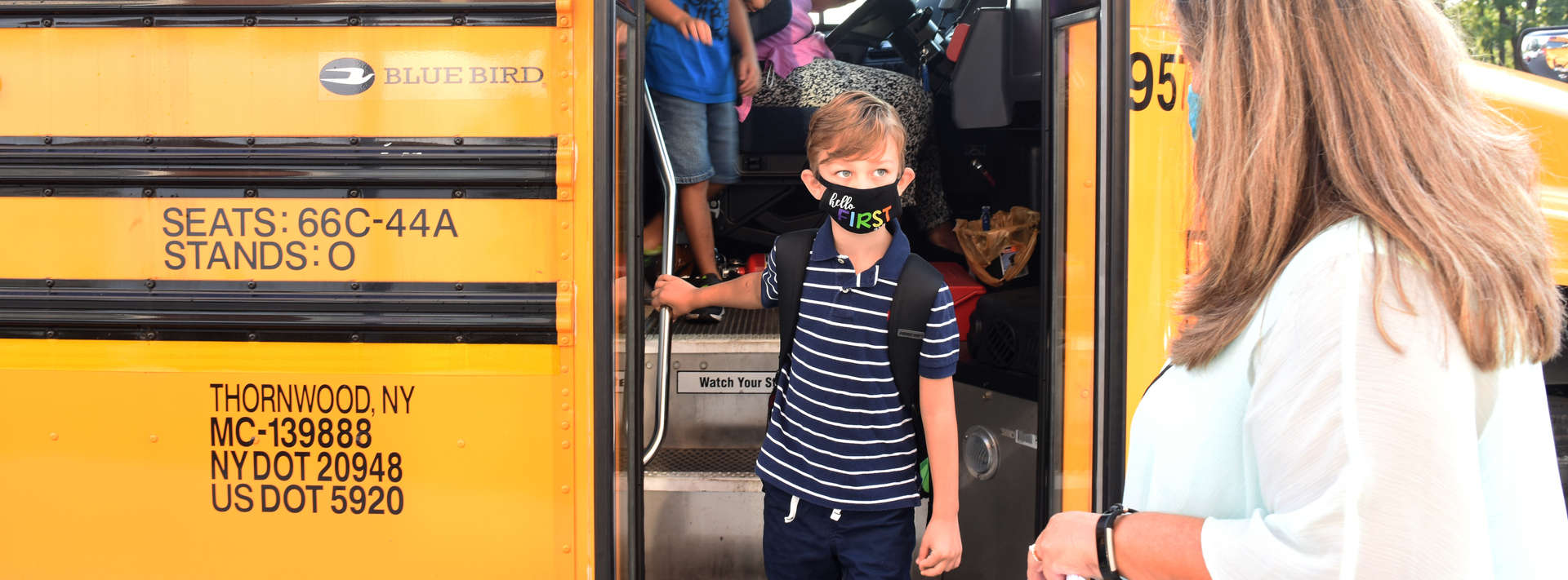 boy in mask gets off the bus