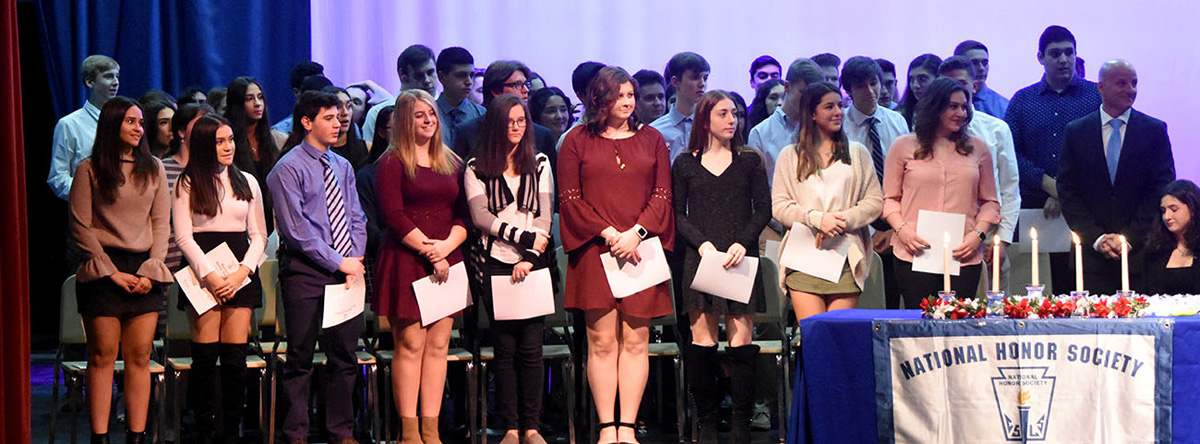 Large group of students stand on stage at National Honor Society induction.