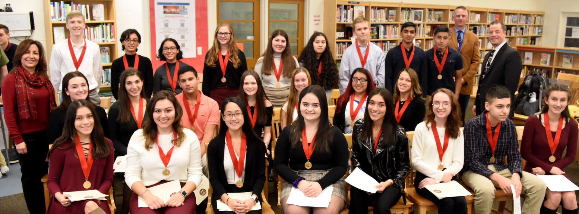 24 students and several teachers pose for photo after Spanish honor society induction