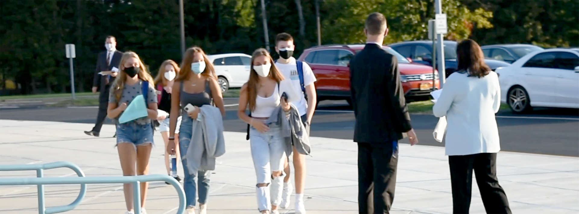 Several girls with masks walking past 2 adults