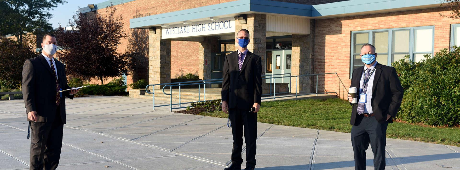 three men standing in front of high school