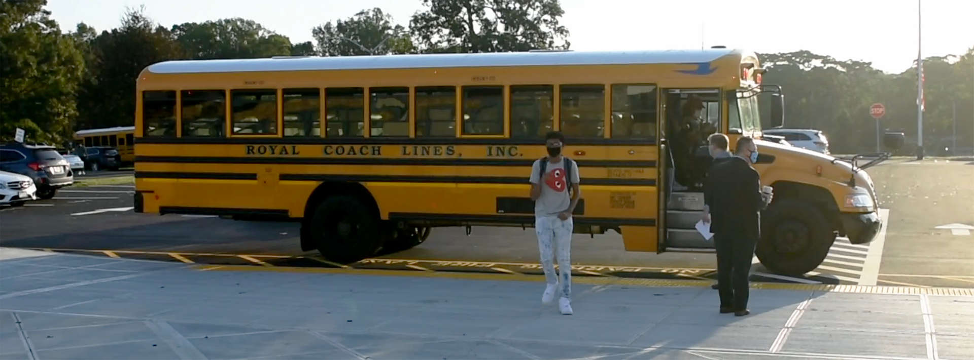 Boy exiting bus parked on curb