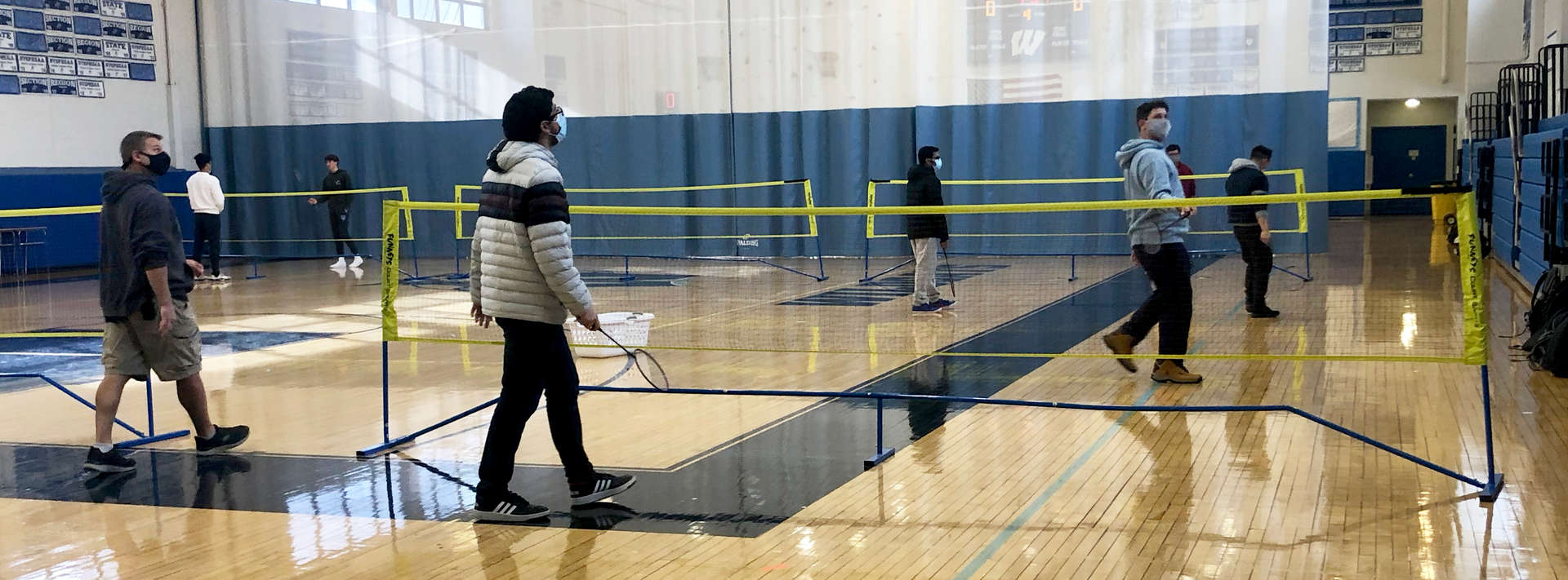 high school students play badminton during PE class