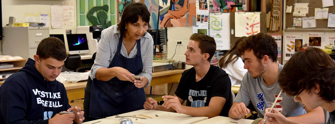 Art teacher working with ceramics students.