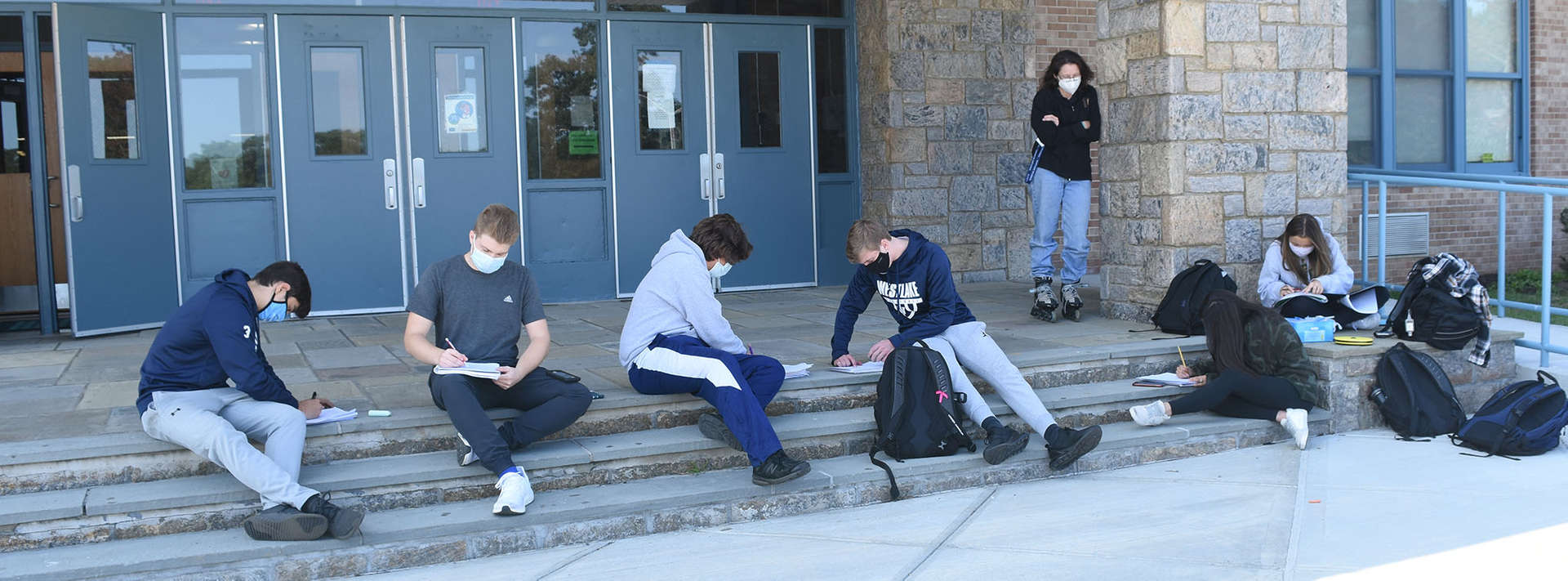 Students sit on front steps of school as teacher looks on.
