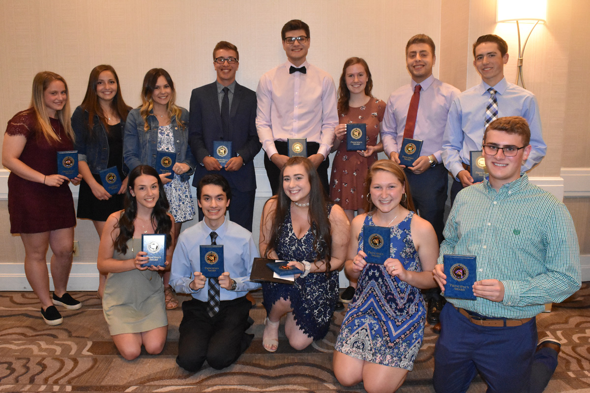 13 students pose with awards