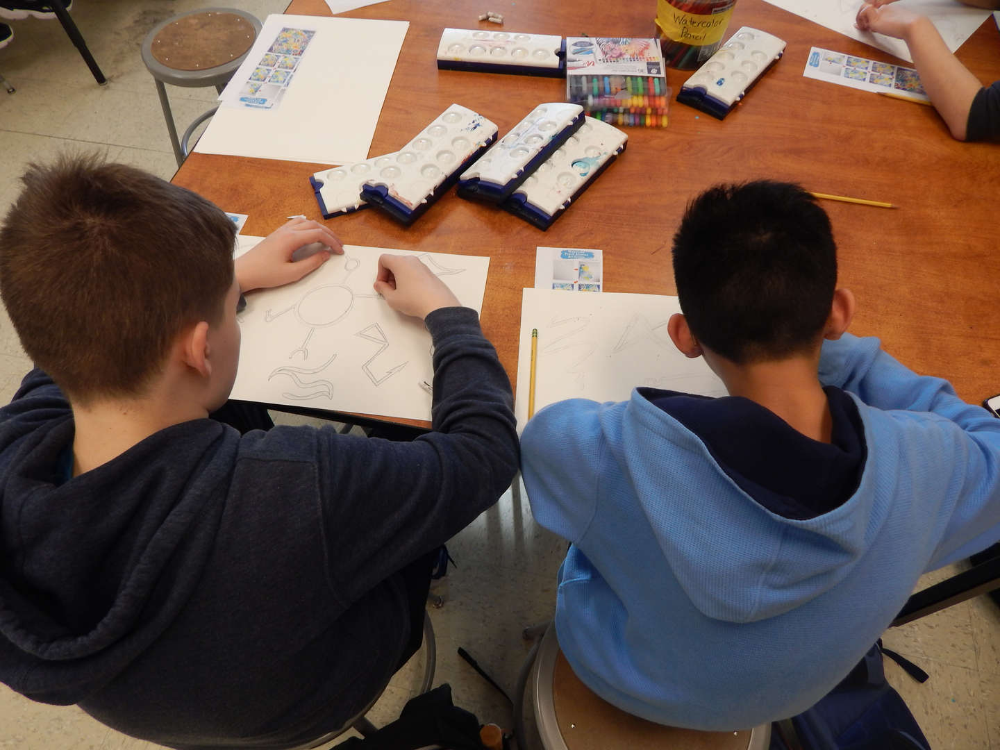 students drawing at a table