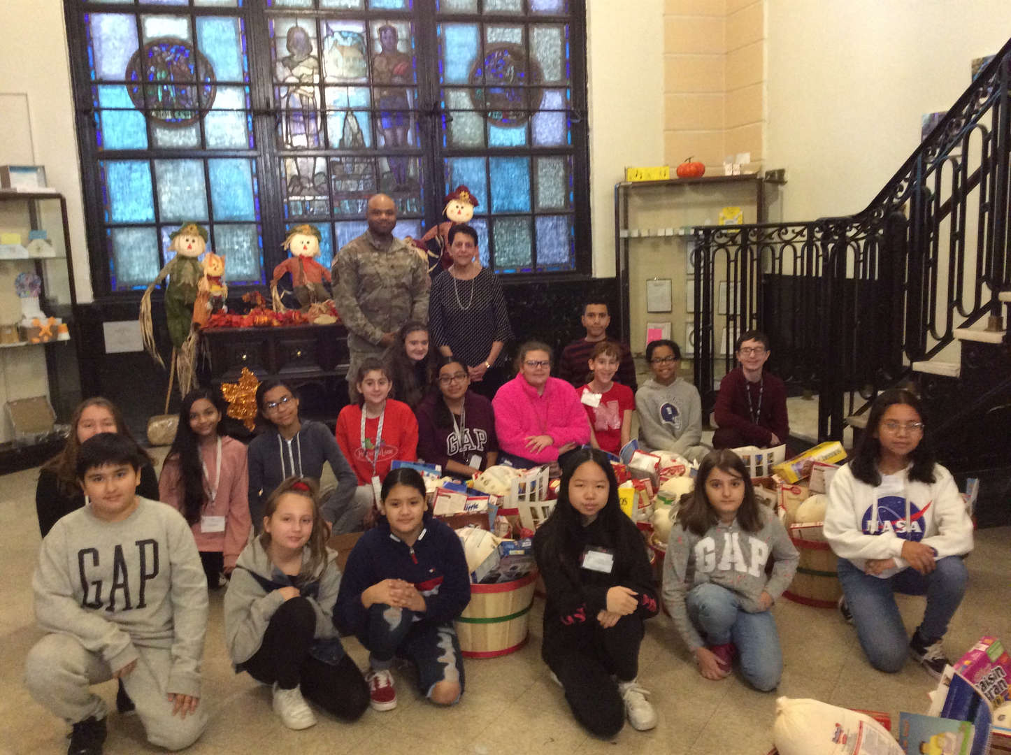 Principal DiBella, US Soldier and PS IS 104 students with all Baskets filled with donated food.