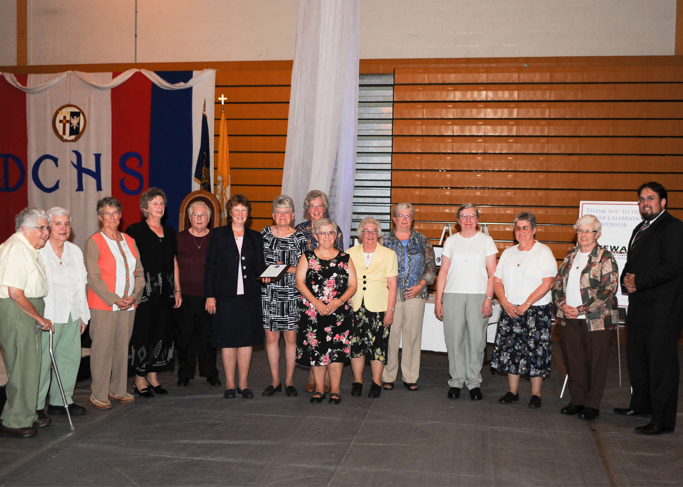 Sister Ann Myers, President of the Sisters of Saint Joseph of Chestnut Hill, Pa., and numerous alumni and former faculty and staff members accept induction on behalf of their congregation.