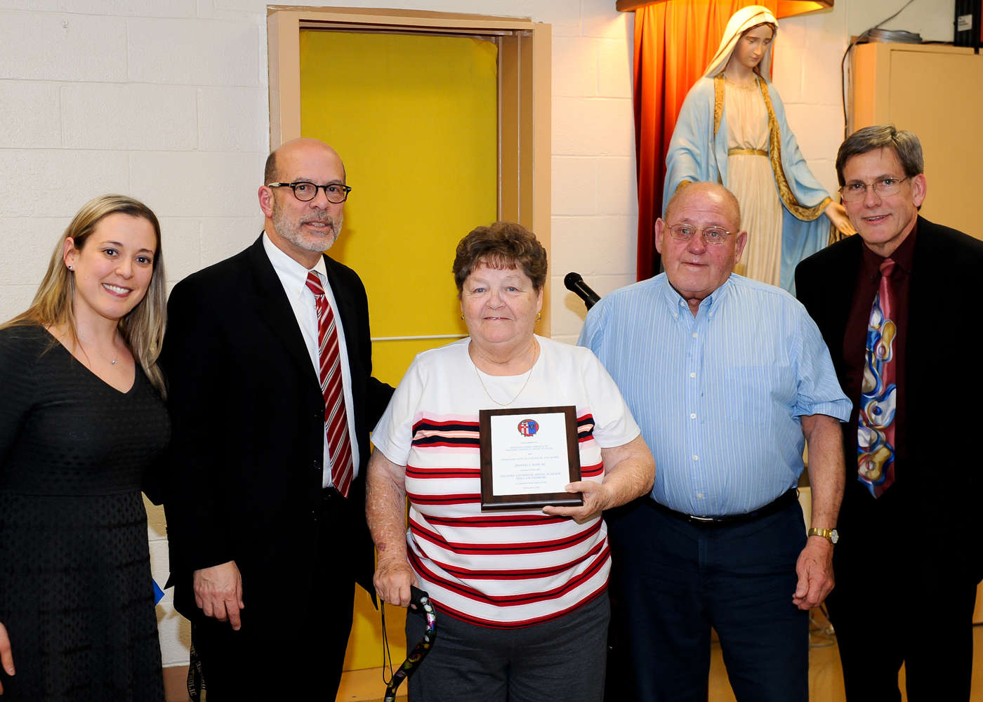 Violet M. (Smith) Bair '60 (center) and Benjamin J. Bair '60 (second from right) accept induction into the Delone Catholic Hall of Honor on behalf of their son, Daniel J. Bair '85.