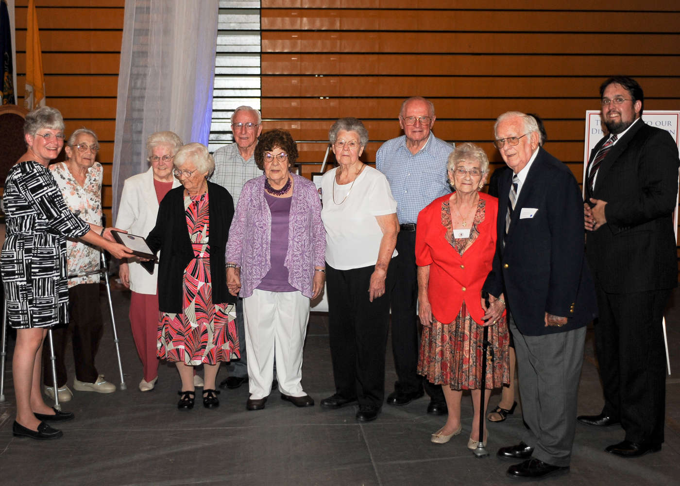 Members of the Delone Catholic Classes of 1941-1944, the first to directly benefit from Mr. Delone's gift, accepted induction on his behalf.