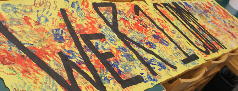 """The theme of HomeBase this year is community. Sixth graders made a handprint mural during orientation, just before school started. It now hangs in the dining room with the words """"We R 1 Community"""" on it for everyone in the school to sign."""