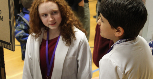 A high school student speaks with a science fair participant