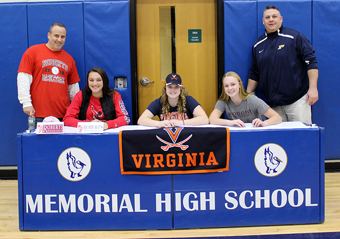 Varsity basketball coach Tim Pitrulle, Samantha Volpe, Jennifer Bell, Lucy Bischof and Athletic Director Steve Luciana are shown sitting at a table in the gym.