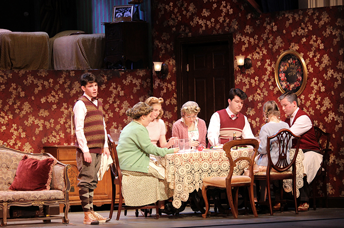 "The cast sits around a kitchen table on the set of ""Brighton Beach Memoirs."""