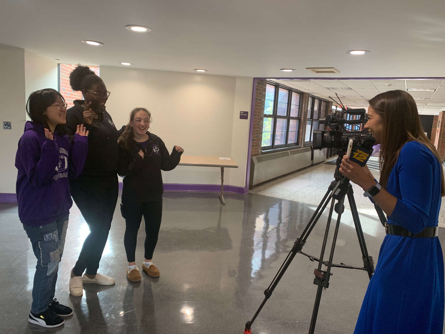 News 12 reporter talking with three New Rochelle High School students.