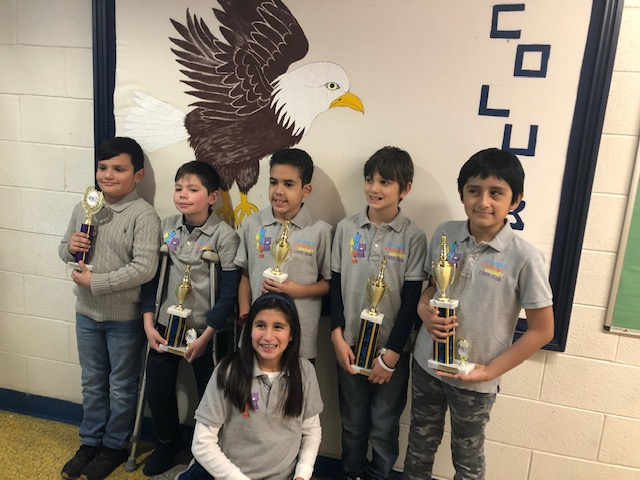 The Columbus School chess team holding trophies