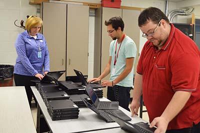 Technology directors fixing computers.
