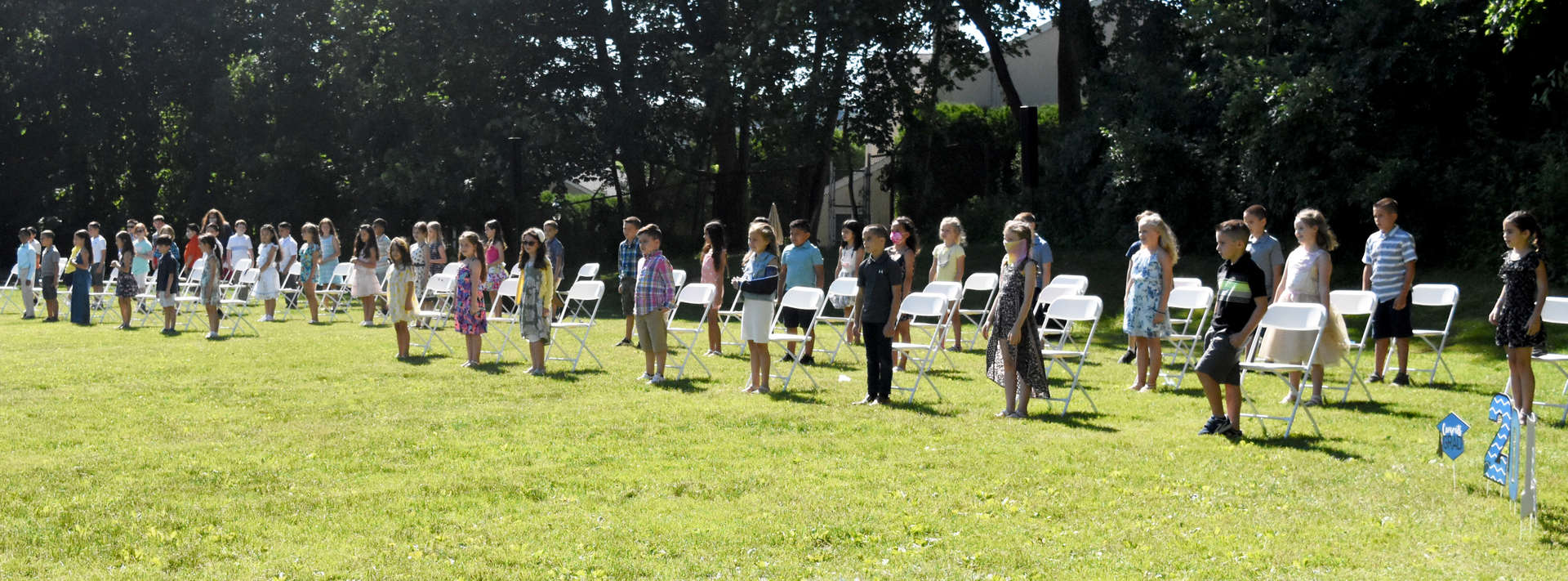 Students lined up in front of rows of chairs at graduation ceremony.