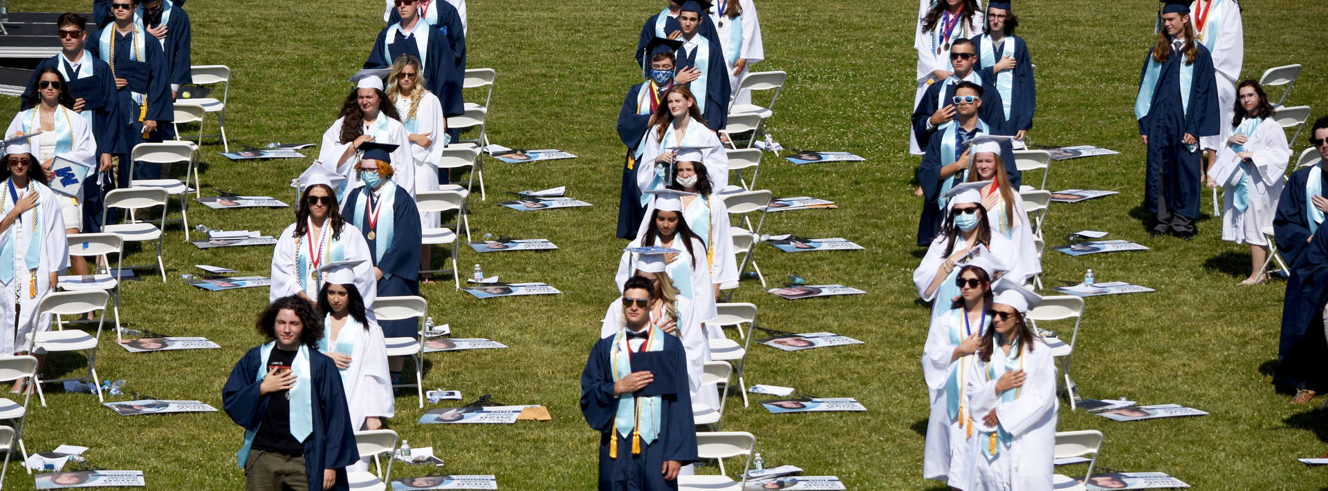 Graduates stand on field saying pledge of allegiance