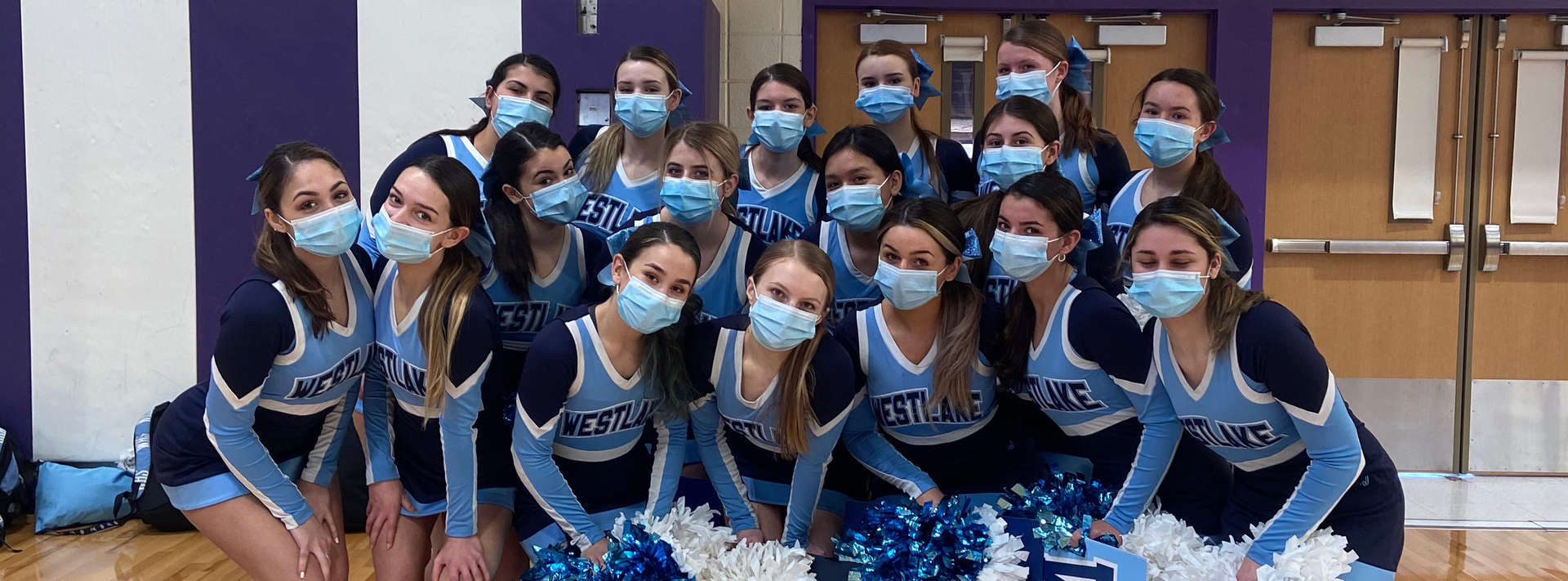Cheerleading team posing with masks