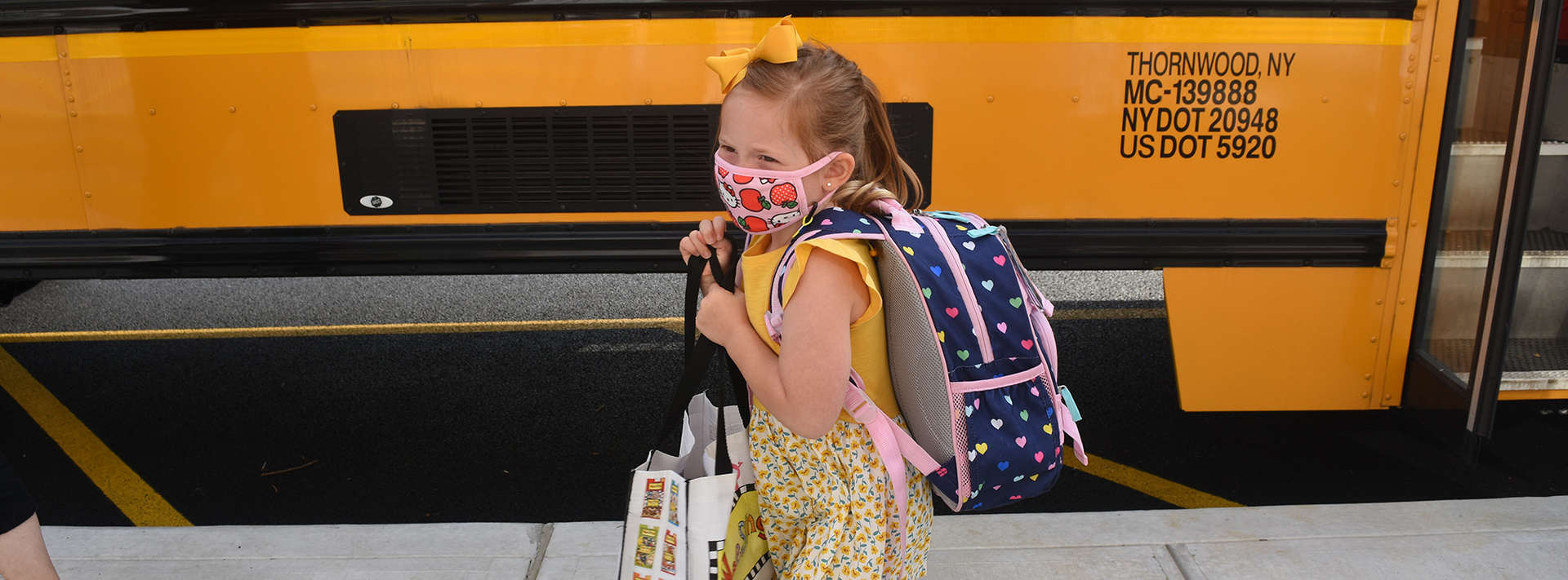 little girl with mask and backpack standing next to bus