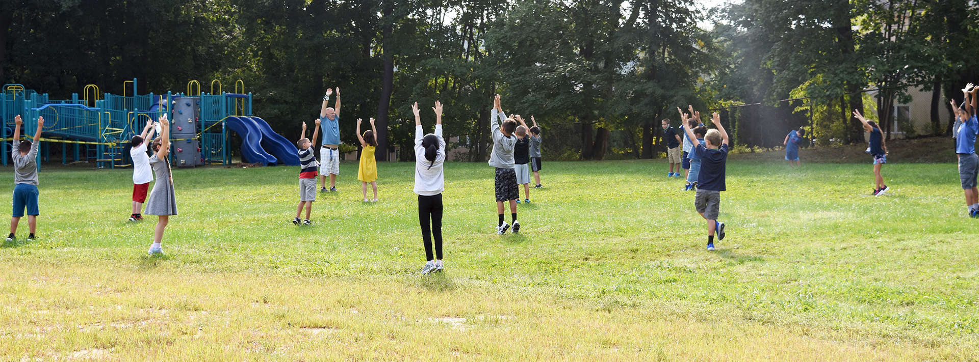 group of PE students on field doing stretches