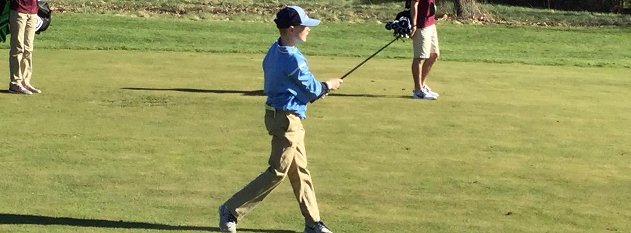 Boy swinging golf club.