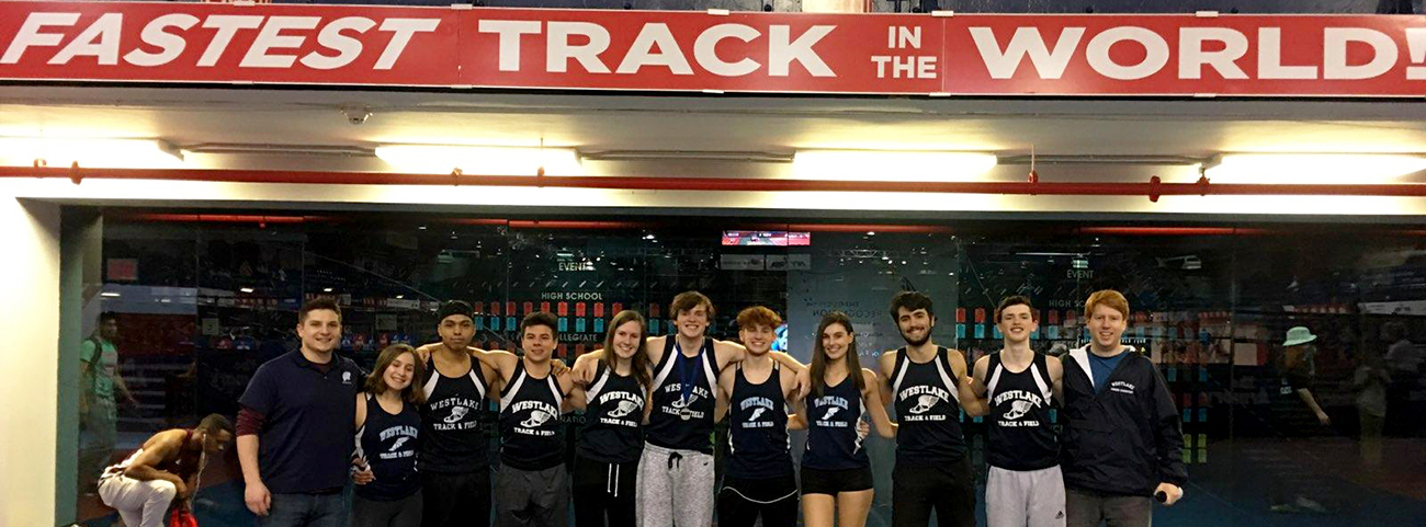 "12 people in track clothes lined up under ""fastest track in the world"" sign"